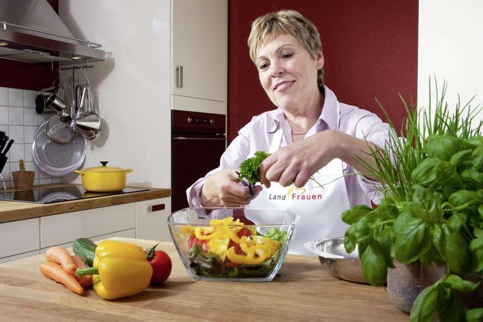 Landfrau Lore Mauler bereitet Salat am liebsten ganz frisch zu, mit Gemüse und Kräutern in kontrollierter Qualität. Foto: djd/www.qs-live.de