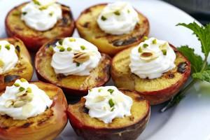 Die Pfirsichhälften erst nach dem Grillen mit Schlagsahne, Pistazien und Mandeln anrichten. Foto: djd/www.qs-live.de